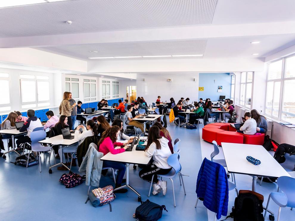 Varios docentes imparten clase a la vez a dos grupos de alumnos en el mismo espacio.