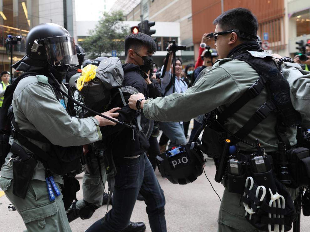 Dos policías retienen a uno de los manifestantes este domingo en las calles de Hong Kong.