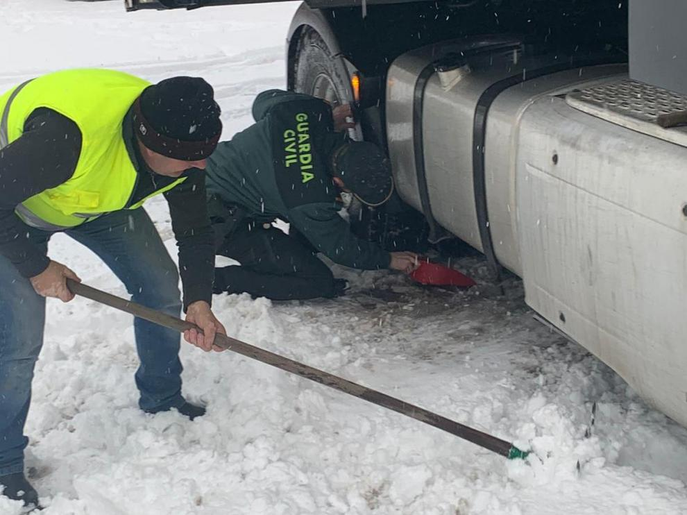 Los agentes de la Guardia Civil que han auxiliado a la mujer embarazada esta mañana ayudan a poner cadenas a otro conductor atrapado por el temporal.
