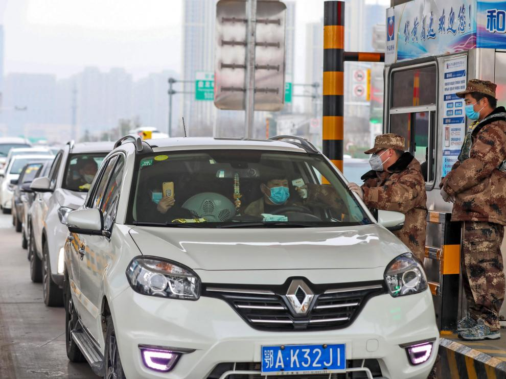 Un militar comprueba la temperatura de dos personas en un coche en Wuhan.