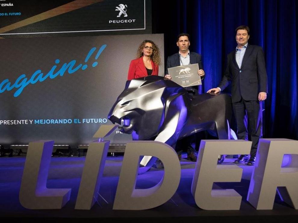 Francisco de Ayerbe (en el centro), gerente de PSA Retail Zaragoza, recibiendo el premio de Helene Bouteleau, directora general de Peugeot España, y Jaime Piedrola, director de ventas de Peugeot España.