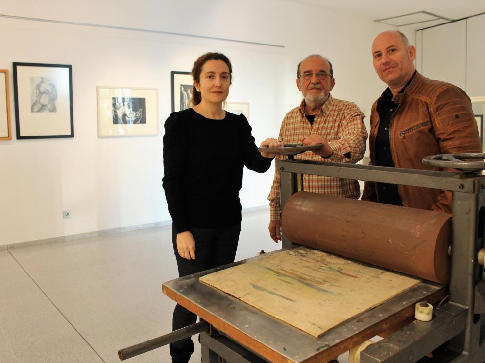 Juan Carlos García (d), Carlos Mas y Laura Baquero, técnico de Cultura del Ayuntamiento de Binéfar, con el tórculo que utilizaba Katia Acín.
