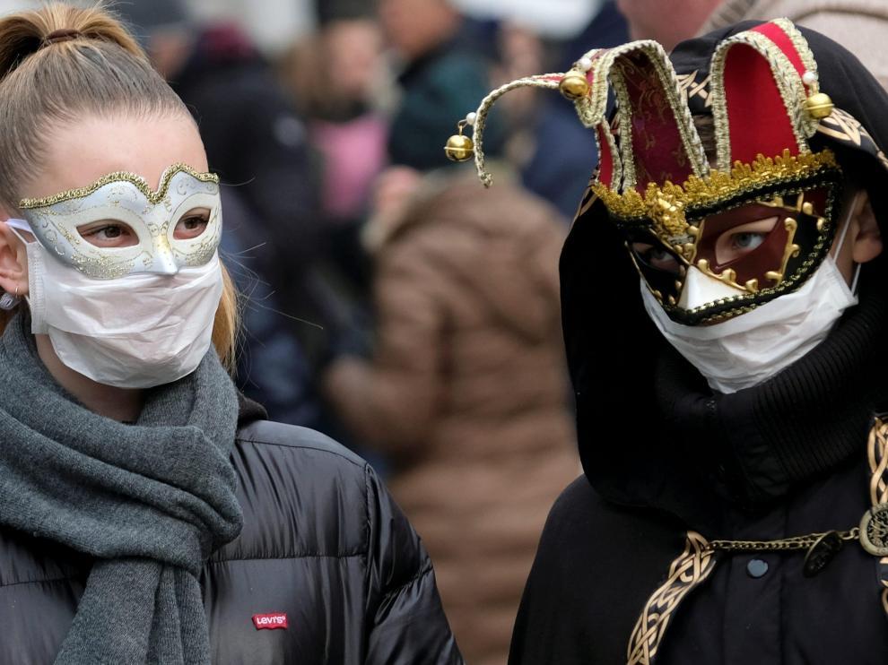Dos personas pasean por Venecia con máscaras de carnaval y mascarillas protectoras.