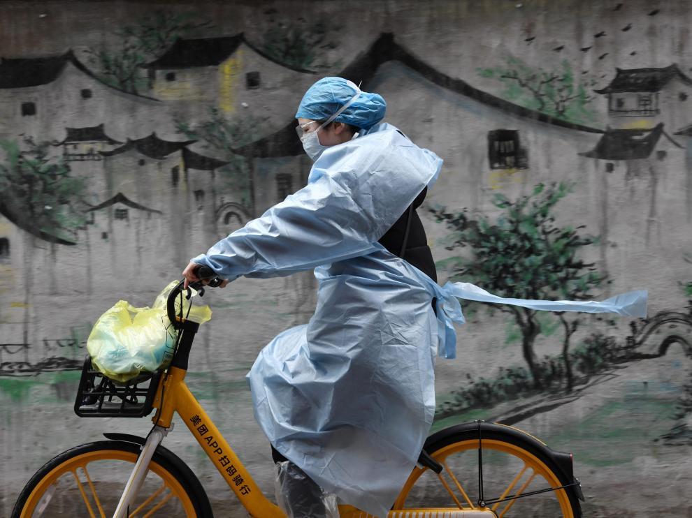 Una mujer en bici se protege del coronavirus en Wuhan, epicentro de la epidemia en China