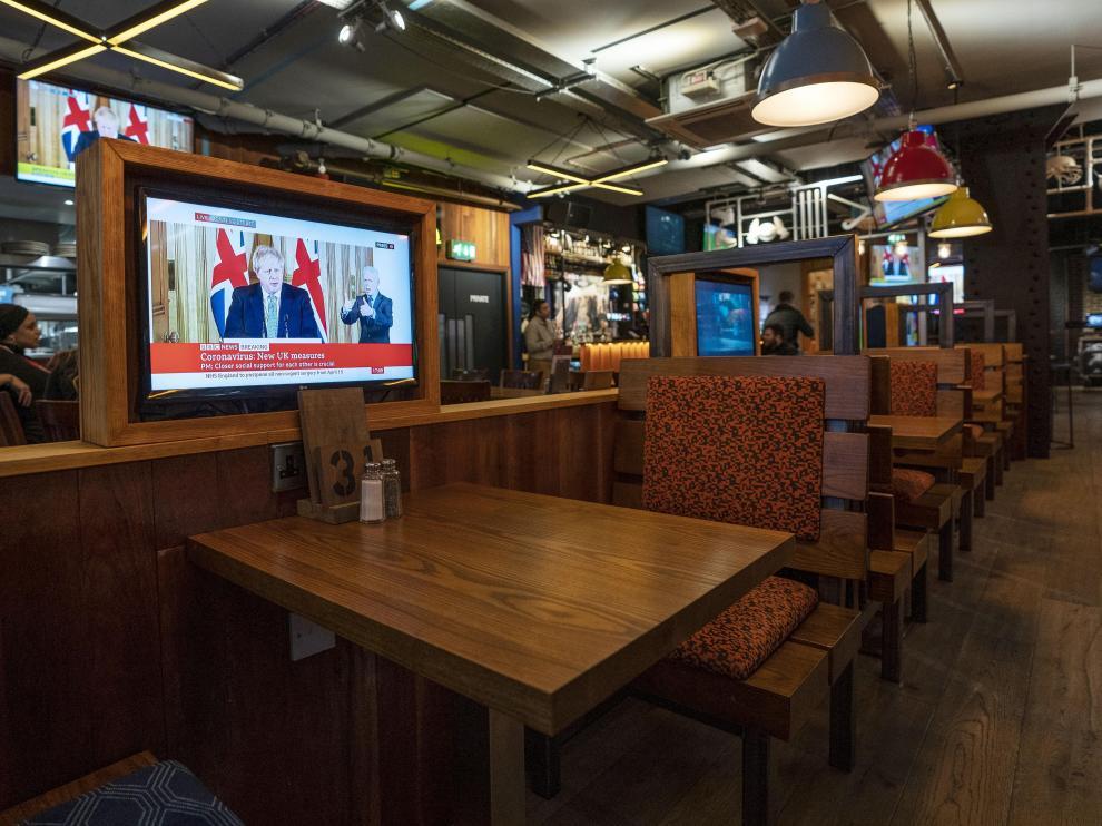 Una televisión muestra una imagen de Boris Johnson en un pub vacío en Londres.