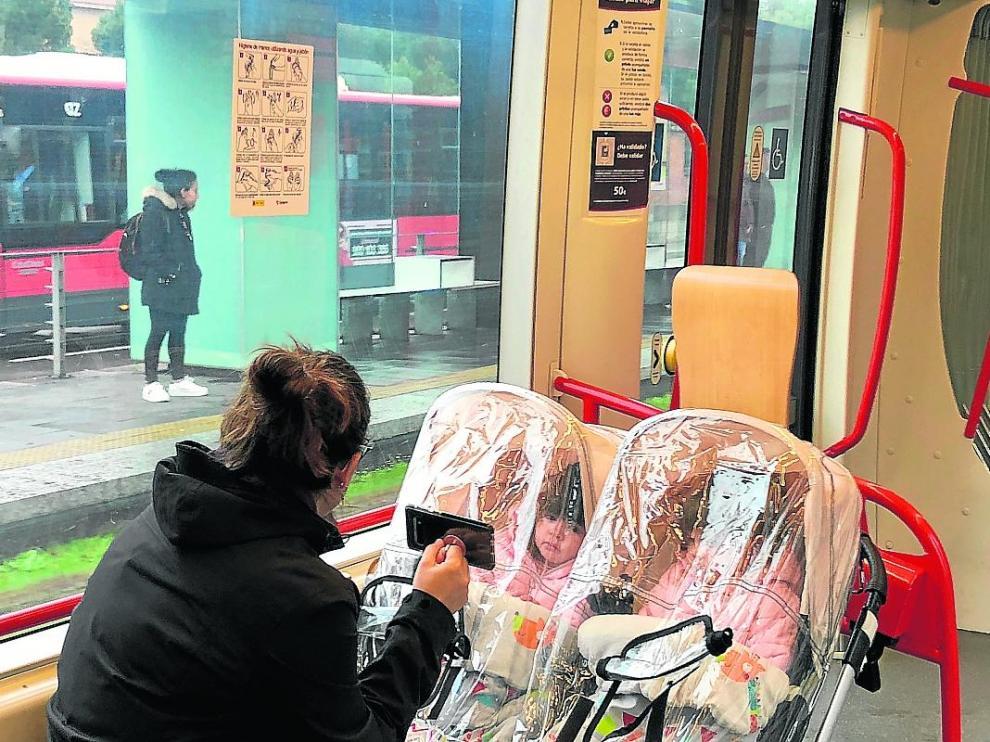 Una mujer y dos niñas, en el tranvía.