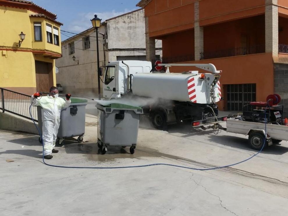 Operarios limpian y desinfectan los contenedores