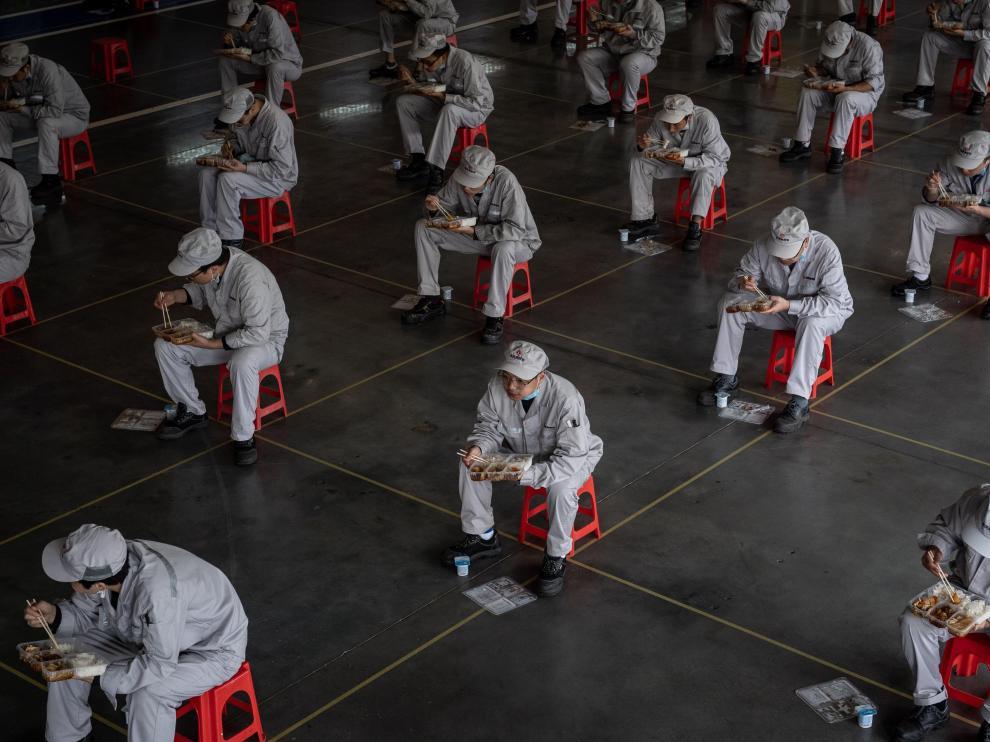 Trabajadores chinos comen en asientos habilitados y colocados para mantener la distancia prudencial recomendada en la fábrica Dongfeng Honda en Wuhan.