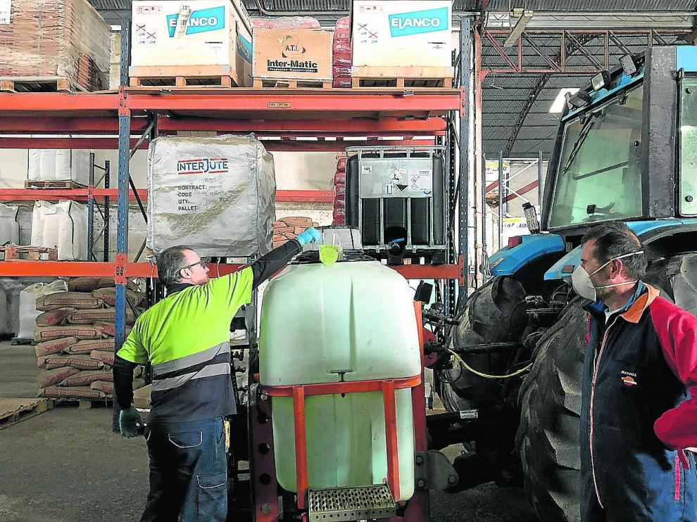 Un cooperativista de la Cooperativa Agrícola San Miguel espera que carguen su atomizador con lejía y agua.