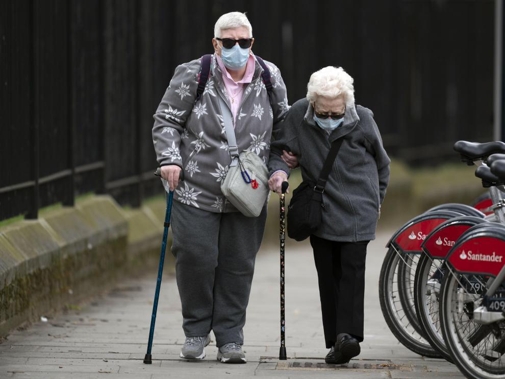 Dos mujeres con mascarillas caminan al lado de un hospital de Londres.