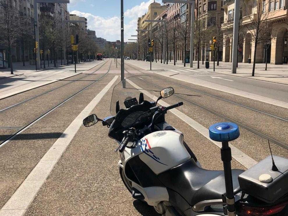 Moto de una patrulla de la Policía Local en un paseo de la Independencia, vacío en Zaragpza