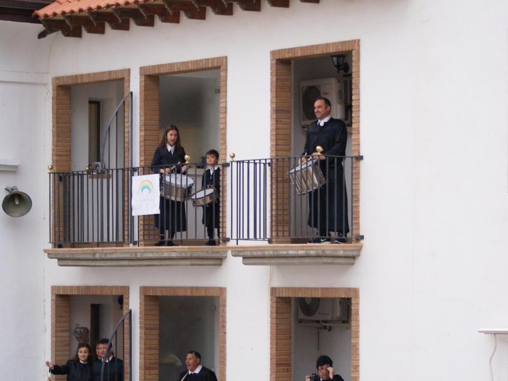 Tocando el tambor y el bombo desde balcones de la plaza del Ayuntamiento de Híjar.
