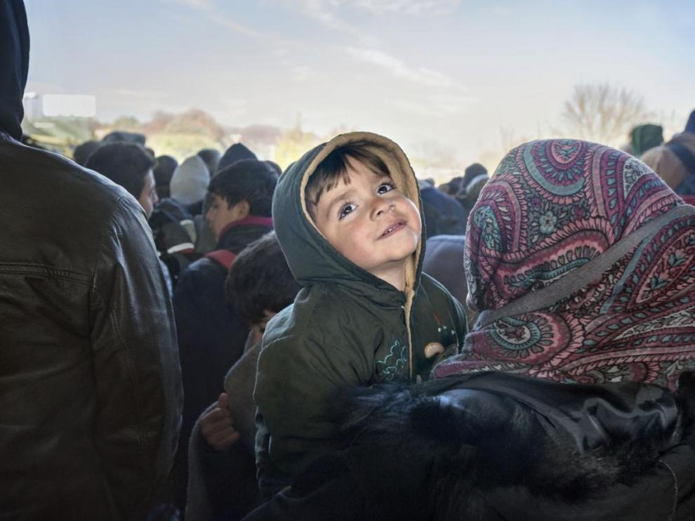 Un niño sirio refugiado sonríe en brazos de su madre en la frontera entre Eslovenia y Austria en noviembre de 2015 Foto: Gervasio Sánchez