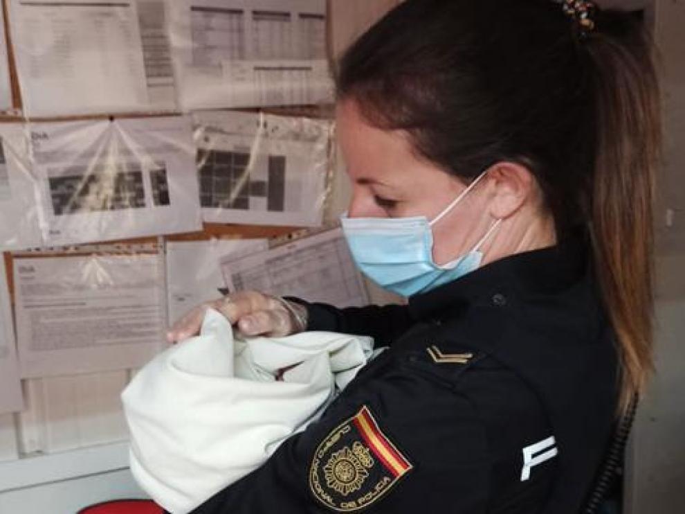 Una agente de Policía con el bebé encontrado en un supermercado de Ávila en brazos