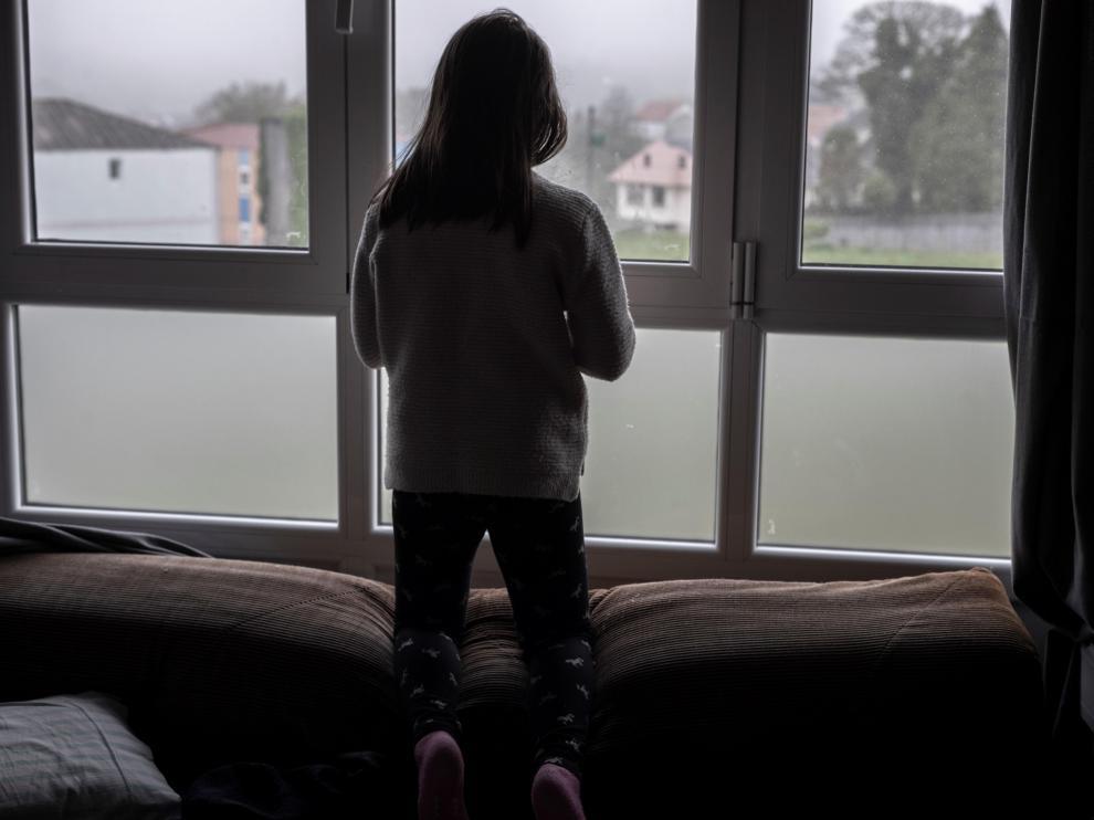 Una niña asomada a la ventana de su casa.