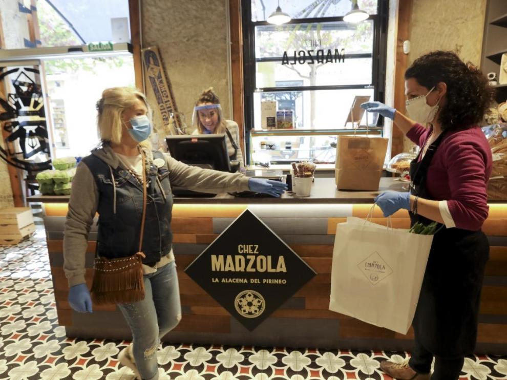 Una voluntaria de la AECC recoge un pedido a domicilio en la tienda de Chez Marzola, de Elena Bernad.