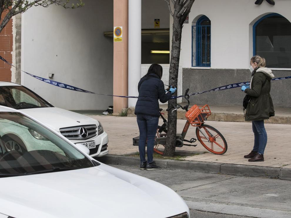 Dos policías examinan la bicicleta que el agresor colocó en la acera.