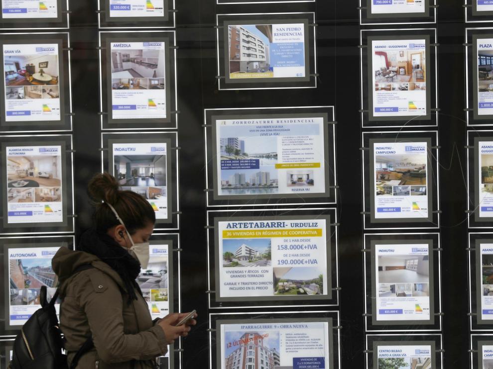 Una mujer pasa por delante de un portal inmobiliario de venta y alquiler en Bilbao este miércoles.