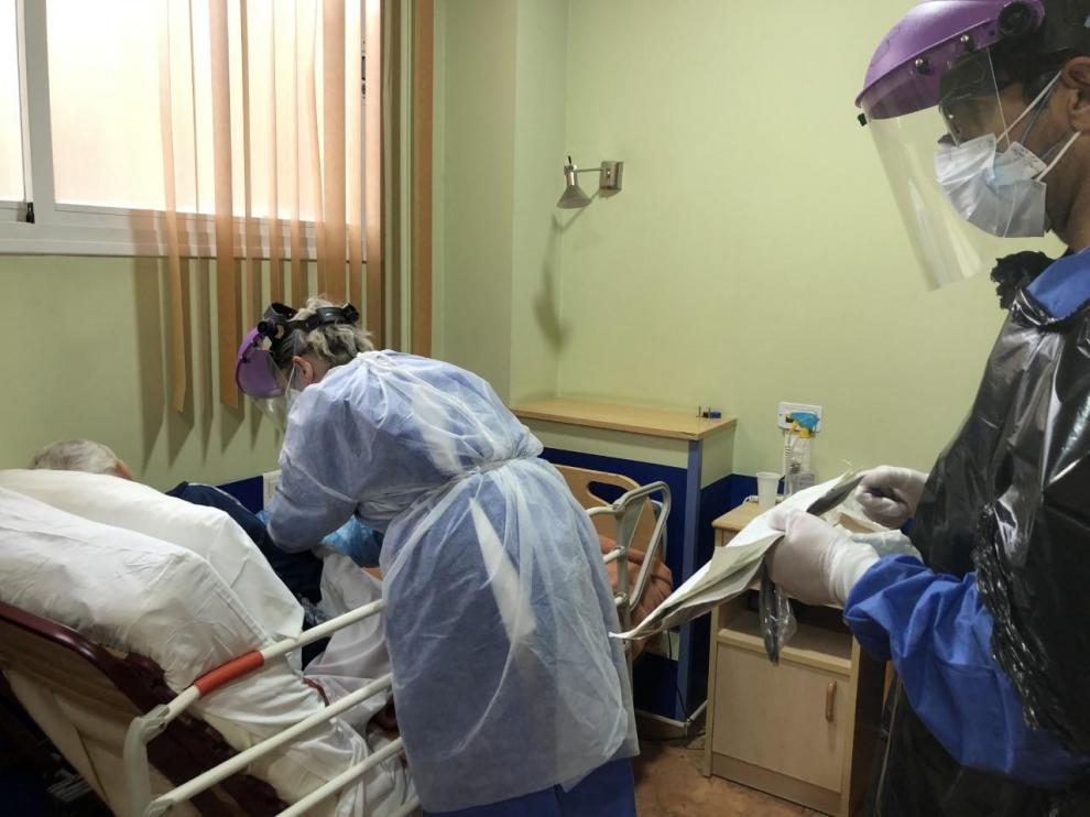 Una doctora y un enfermero atienden a un anciano con coronavirus