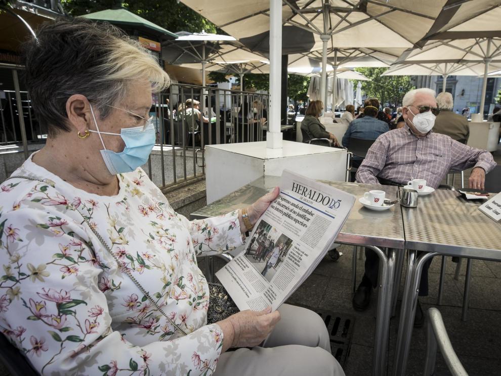 Una pareja lee la prensa mientras toma un café, en una terraza de Zaragoza