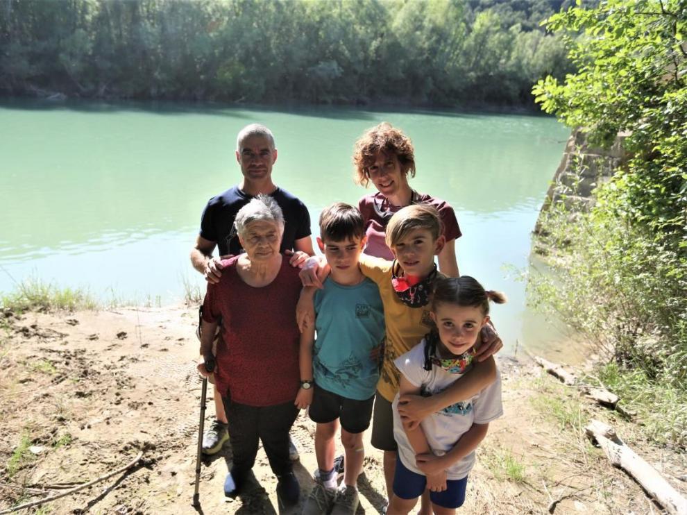 Gustavo e Inés con sus tres hijos y la madre de él, María Ángeles, junto al río en Biscarrués.