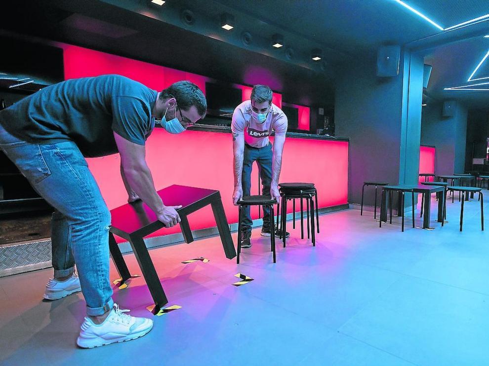 Trabajadores del Hïde Club preparan las mesas en la pista de baile para abrir el viernes.