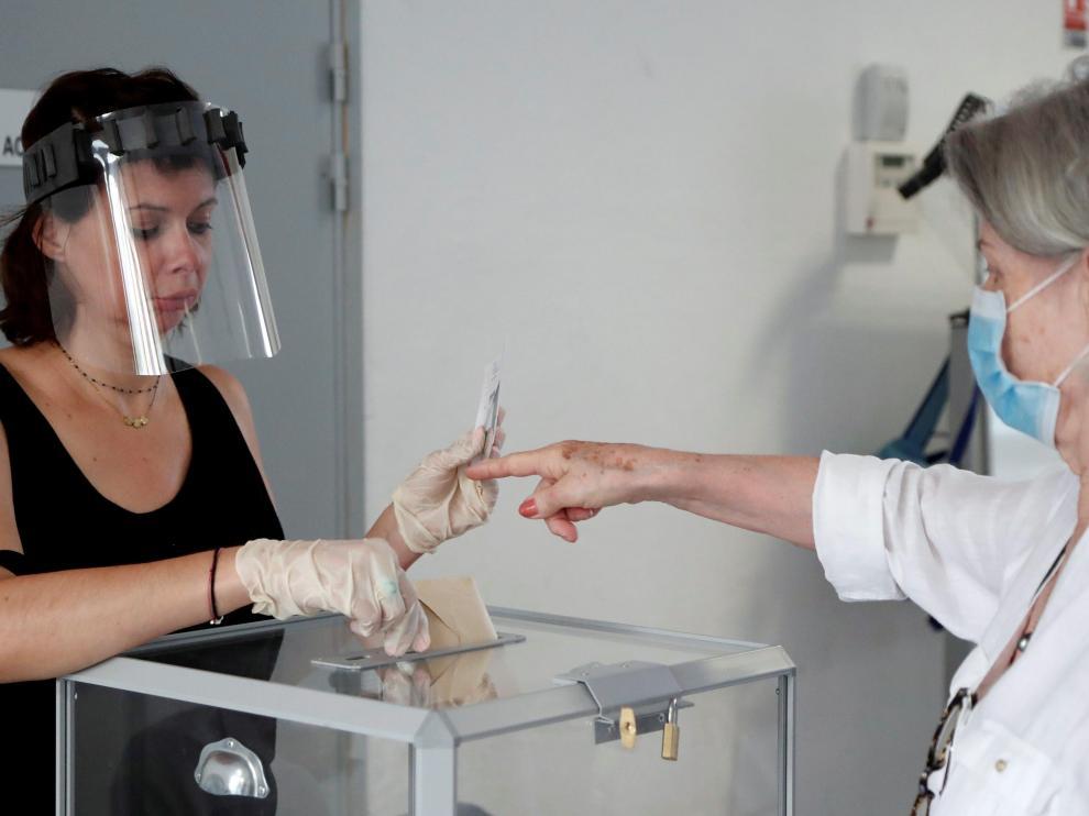 Una persona vota en Perpiñán con las medidas de seguridad recomendadas.