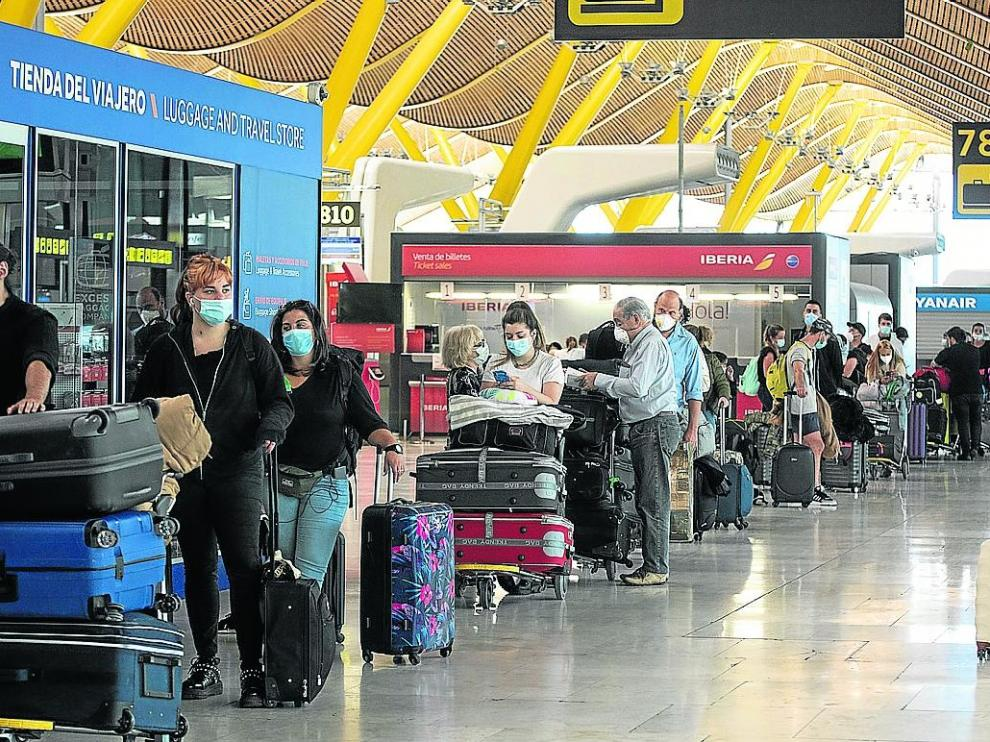Viajeros esperando para facturar sus maletas en el aeropuerto de Barajas, en Madrid.