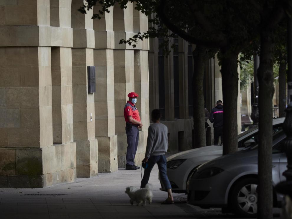 Un agente de la Policía Foral con mascarilla en los soportales de una céntrica calle de Pamplona.