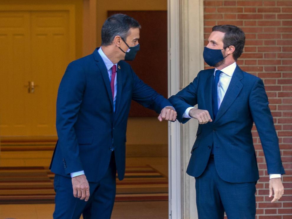 Pedro Sánchez y Pablo Casado se saludan con el codo antes de la reunión de este miércoles.