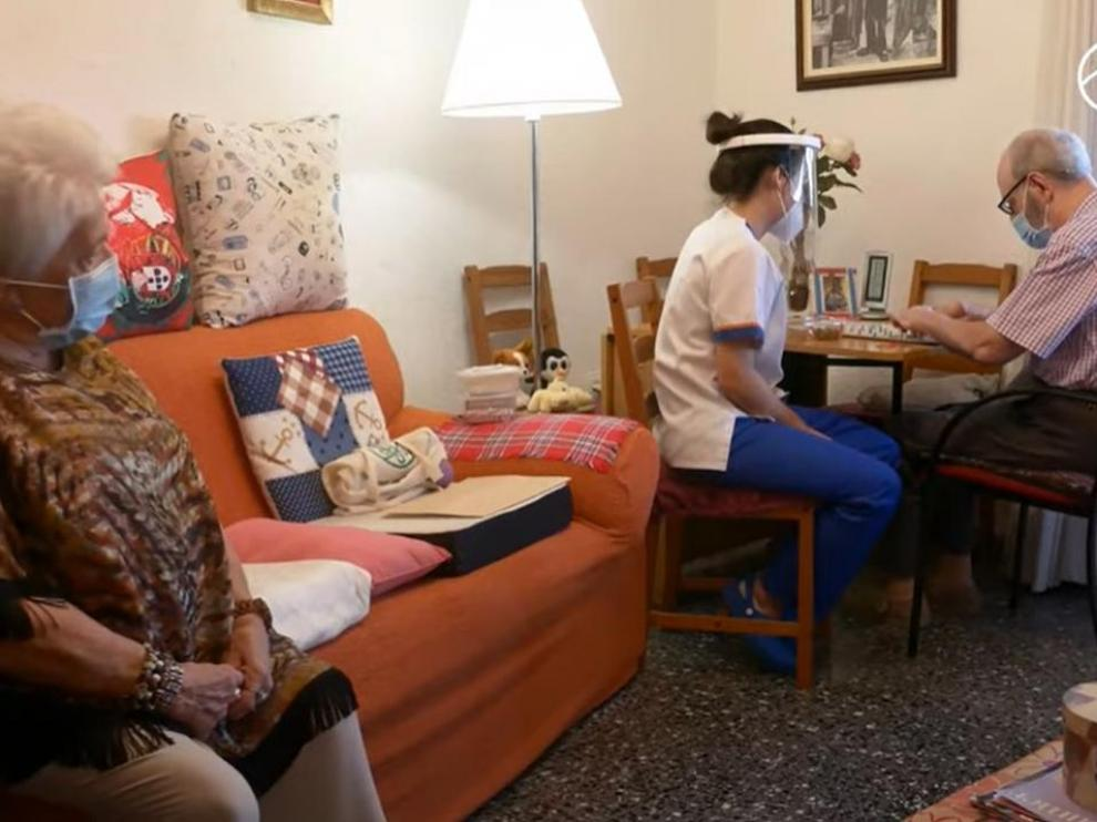 Mercedes Alcázar, en su casa, con marido Paco atendido por una trabajadora del Centro Alzheimer Huesca.