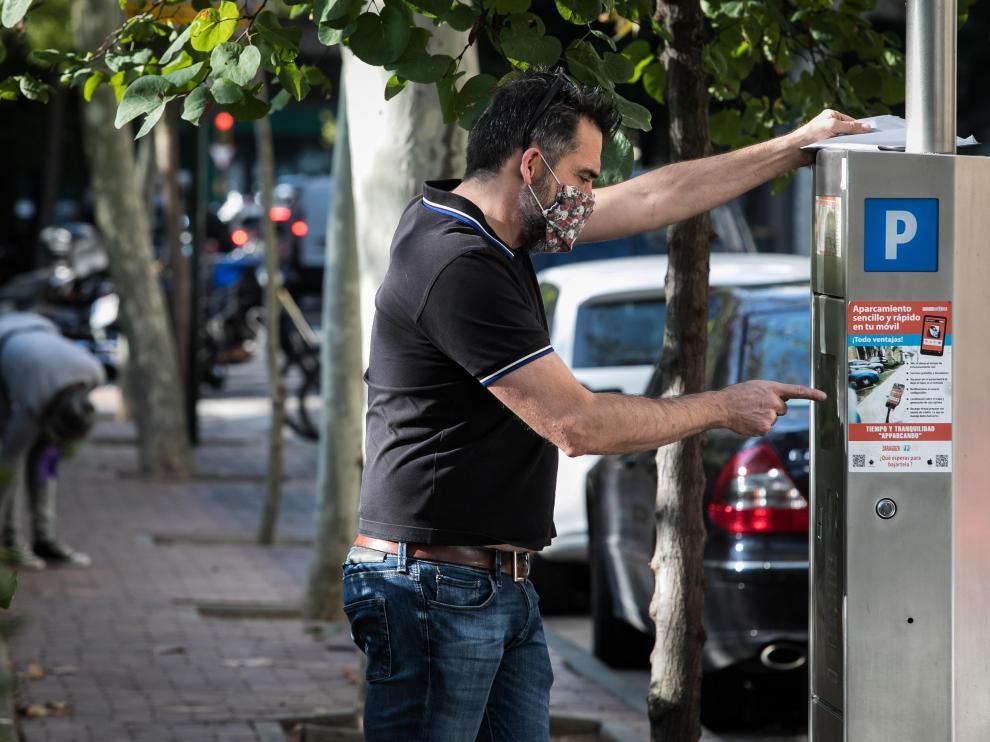 Un usuario paga este miércoles en la zona azul de Zaragoza.