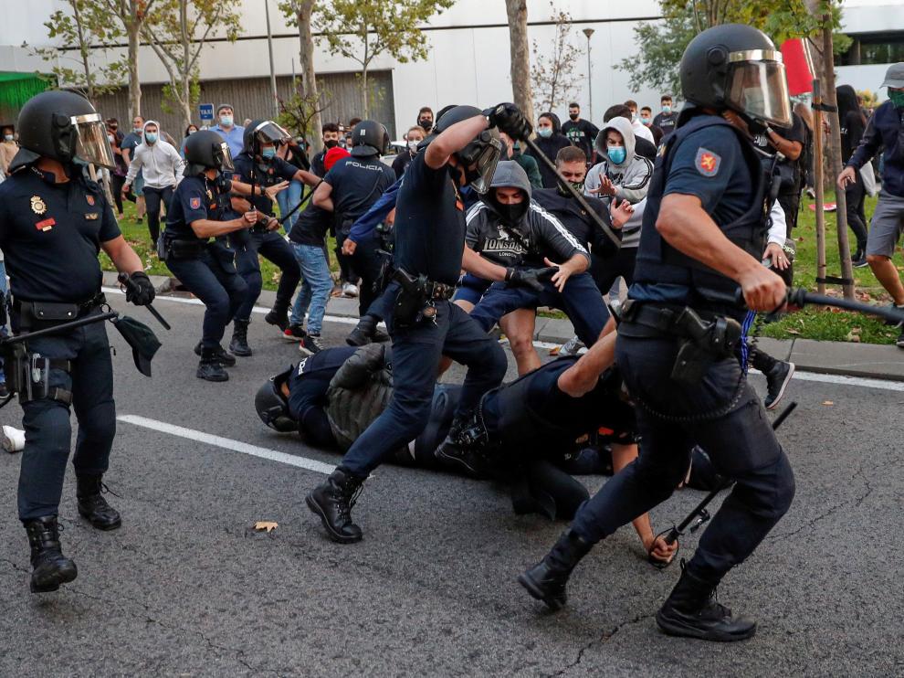 Miembros de la policía cargan contra un grupo de manifestantes que protestaban en favor de la Sanidad Pública y contra los confinamientos selectivos