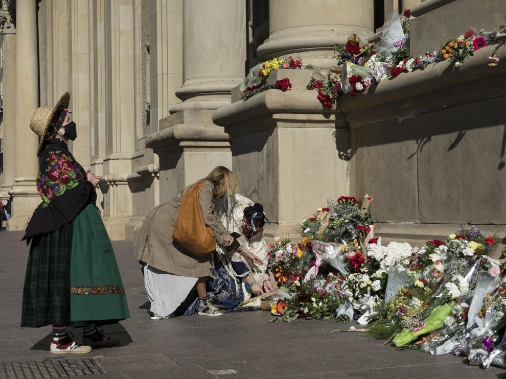 Algunas personas se acercaron ayer al conjunto escultórico de la fachada del Pilar a depositar ramos de flores.