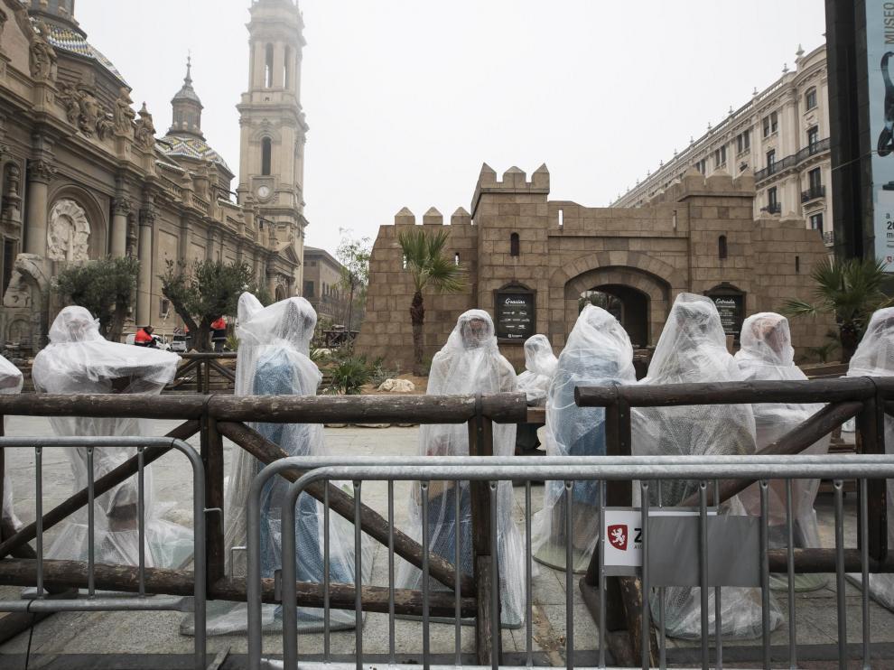 Las figuras del Belén del Pilar, protegidas por plásticos, durante el desmontaje.