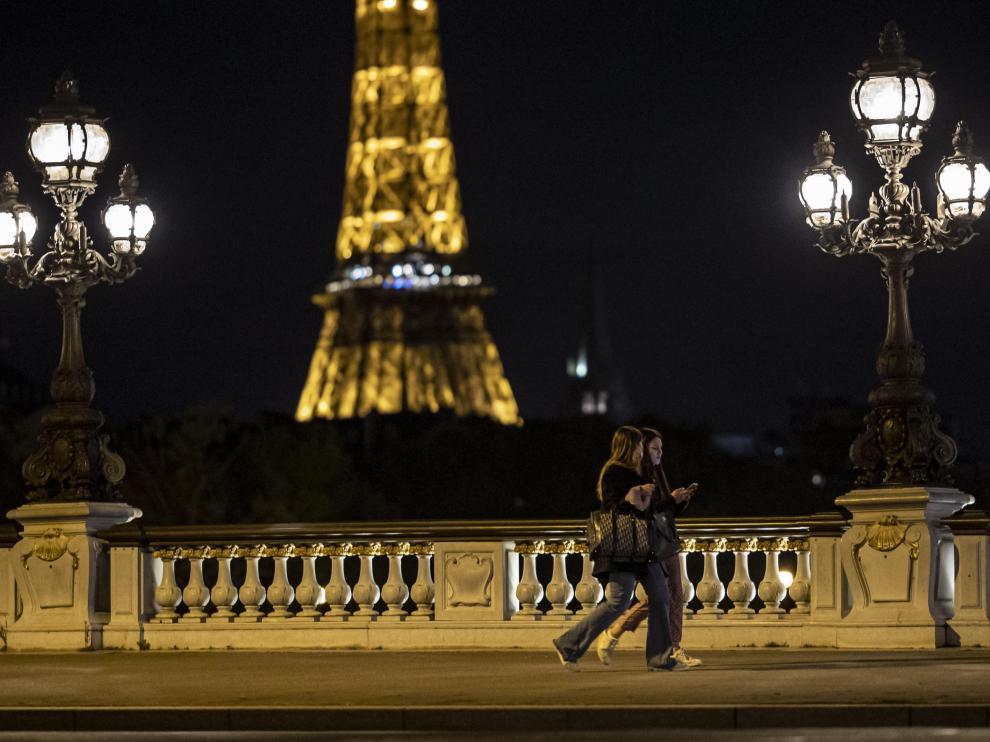 Dos jóvenes caminan por París momentos antes del inicio del toque de queda en la ciudad.