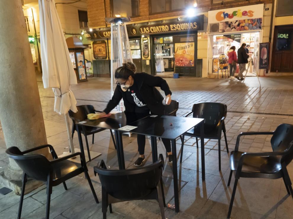 Una trabajadora recoge mesas de un bar de la calle de San Juan de Teruel