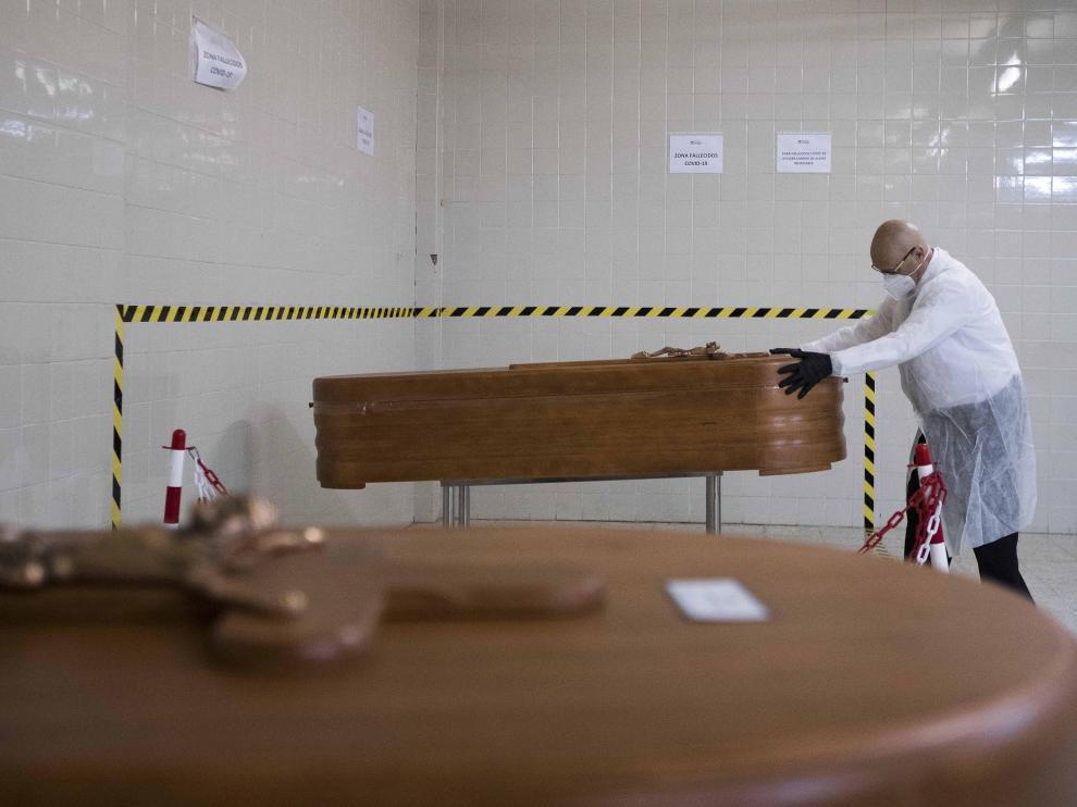 El empleado de una funeraria coloca un féretro con un fallecido por covid en el tanatorio de Torrero de Zaragoza.