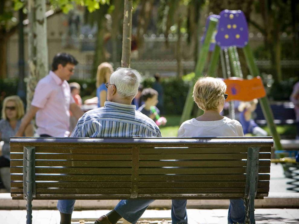 Una pareja sentada en un banco en Zaragoza.