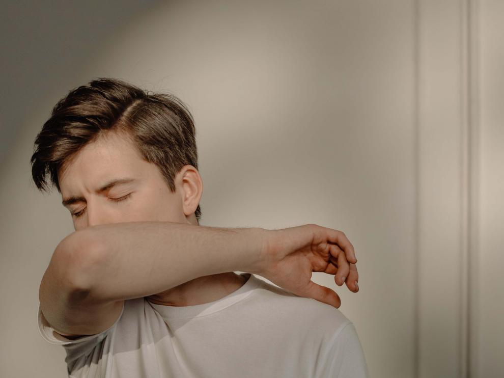 Un joven tosiendo