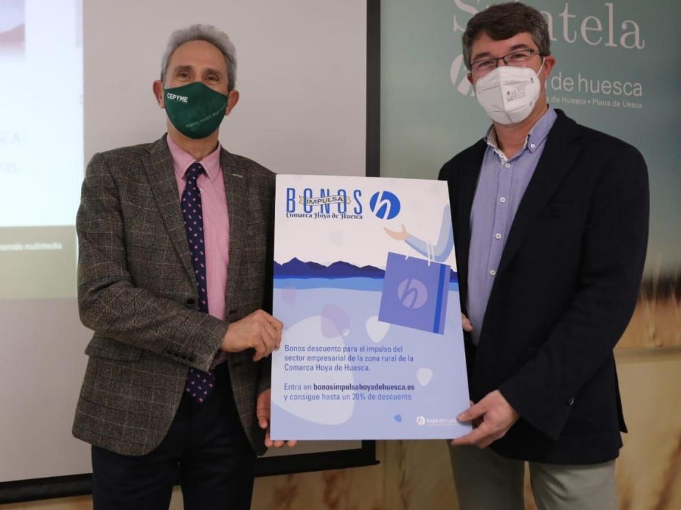 Salvador Cored, director general de la CEOS, y Sergio Moreu, consejero de Desarrollo de la Comarca Hoya de Huesca, con el cartel de la campaña.