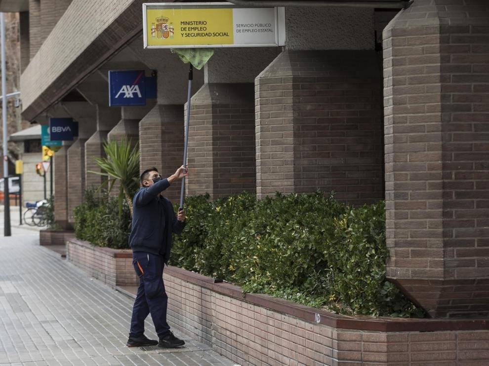 Un operario limpiaba esta miércoles por la tarde el cartel de la sede central del SEPE en Zaragoza, ubicada en Tenor Fleta.