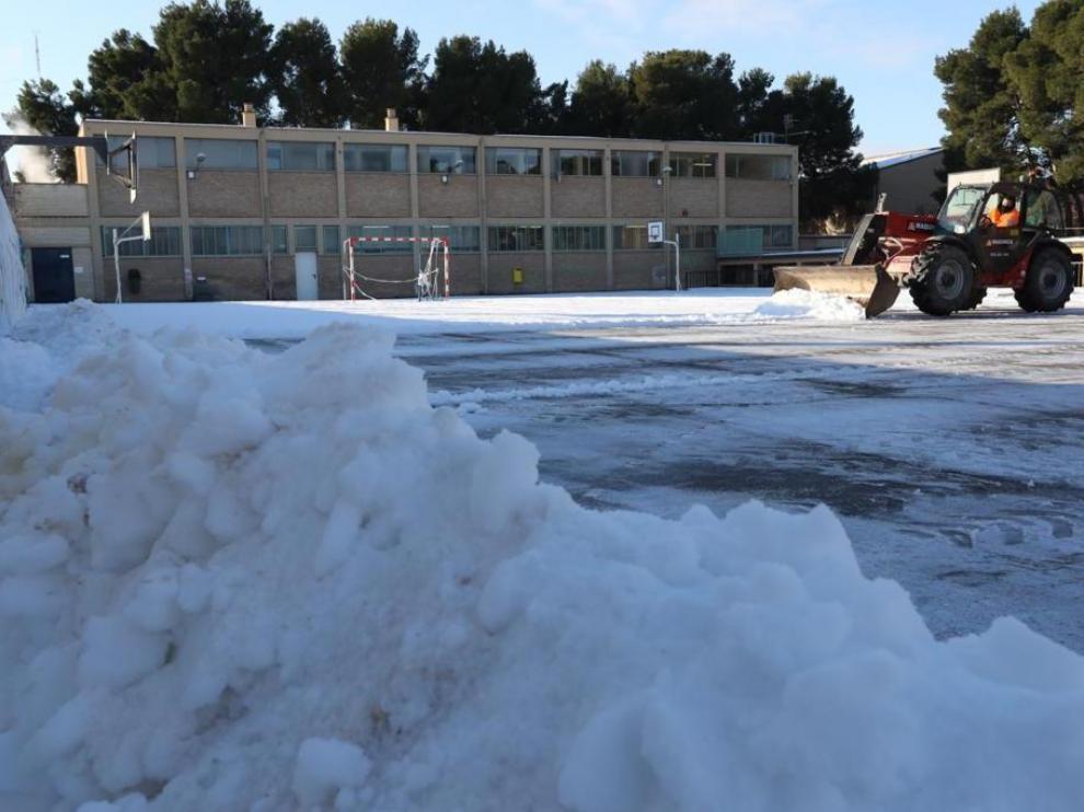 Limpieza este martes de la nieve dejada por la borrasca Filomena en un colegio en Zaragoza.