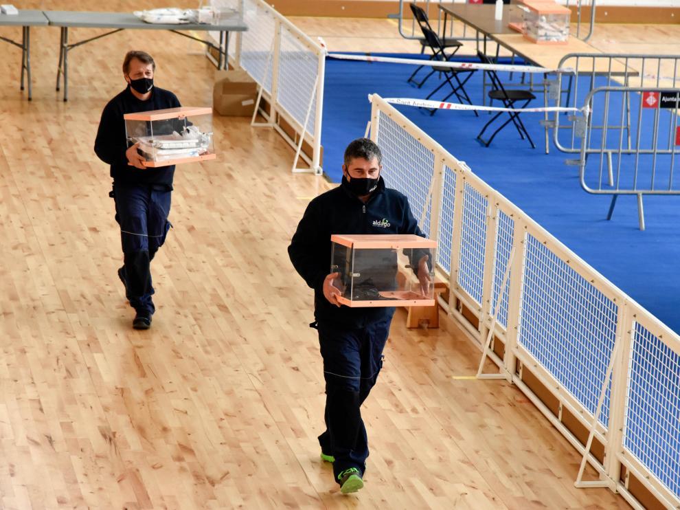 Dos trabajadores transportan urnas en el dispositivo electoral para los comicios catalanes, este sábado en Barcelona.