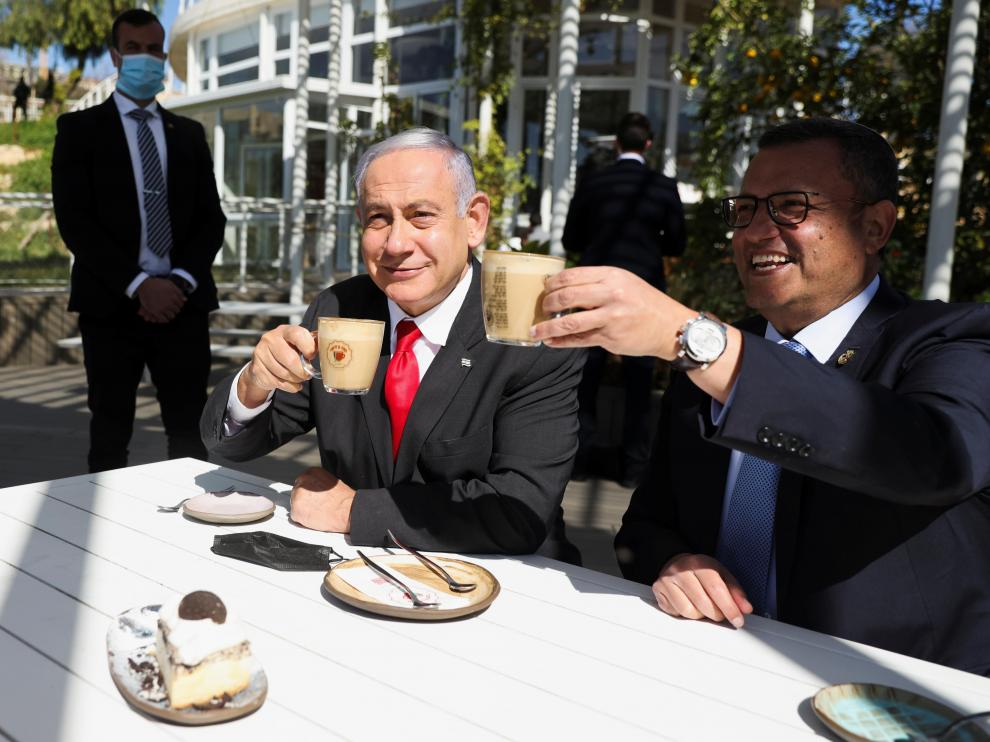Israeli Prime Minister Benjamin Netanyahu drinks coffee with Mayor of Jerusalem, Moshe Leon, as they sit at a cafe while Israel further eases coronavirus disease (COVID-19) restrictions in Jerusalem