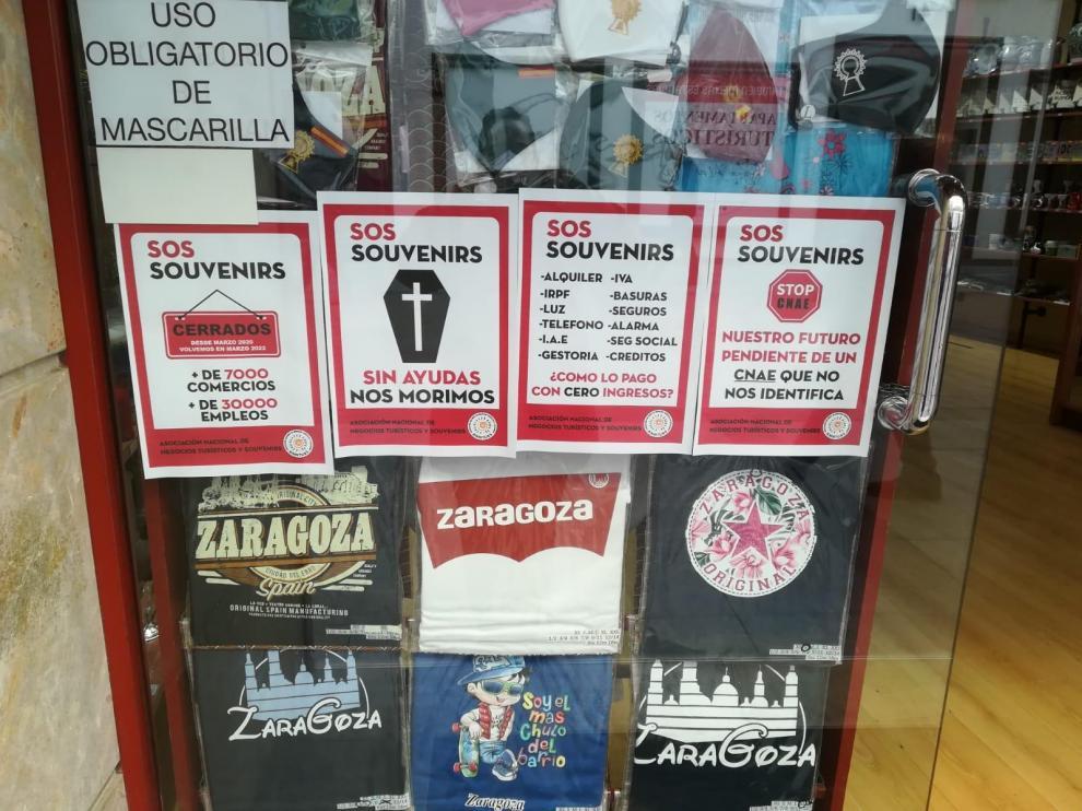 Carteles denunciando la difícil situación económica que atraviesa el sector, en el escaparate de una tienda de Zaragoza.