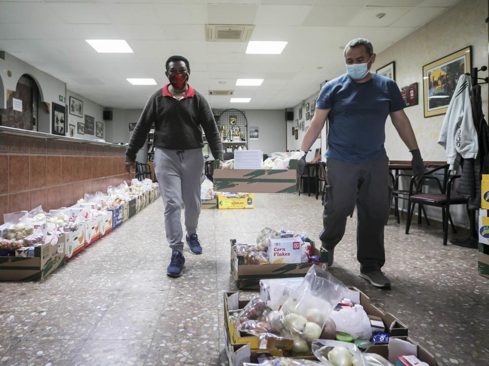 Dos voluntarios mueven un lote de comida para el reparto de la asociación Civitas de Las Fuentes.