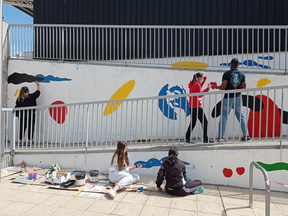 Los alumnos, manos a la obra para crear una obra de arte ambiciosa, una pintura mural en el patio del instituto, diseñada por Samuel Akinfenwa Onwusa