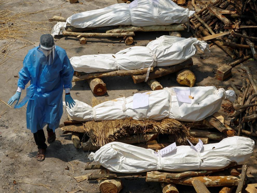 Un sanitario indio pasa entre cadáveres de fallecidos por covid.