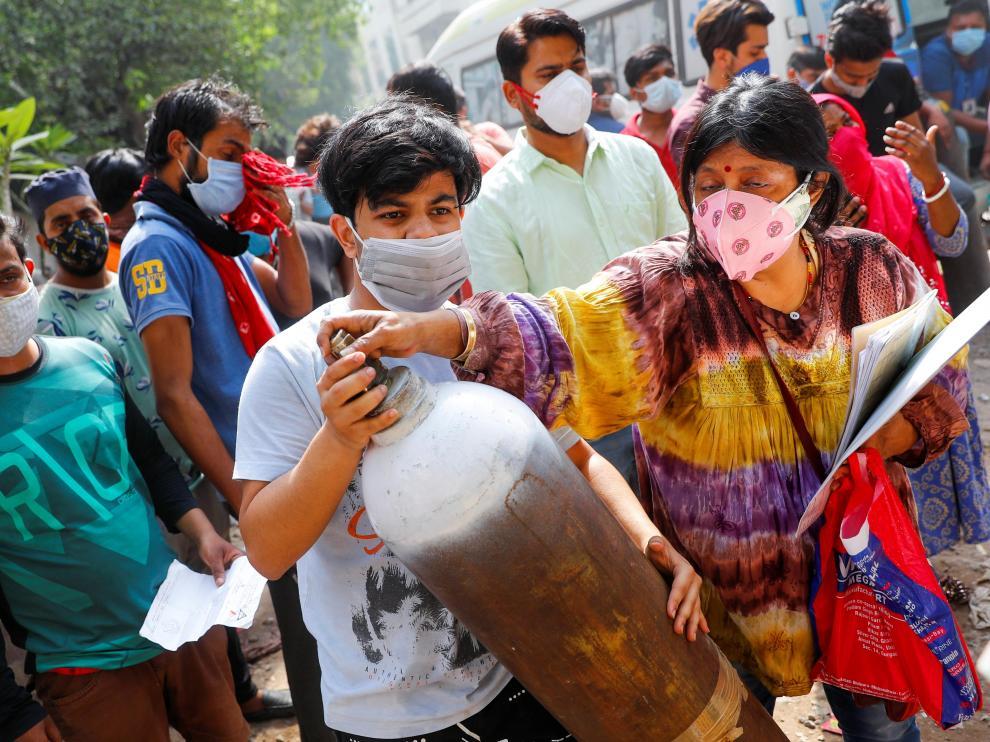 Una mujer y su hijo portan una bombona de oxígeno para recargarla en Nueva Delhi.